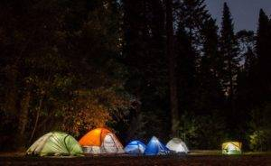 illuminated camping tents at night powered by quiet generators