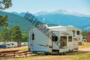 rv set in campsite with large air conditioners on the roof
