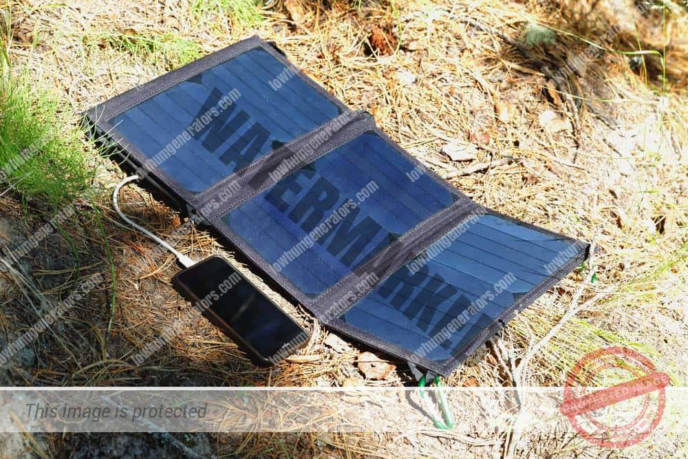 folding solar panel set on the ground as a source of electricity for charging gadgets while camping